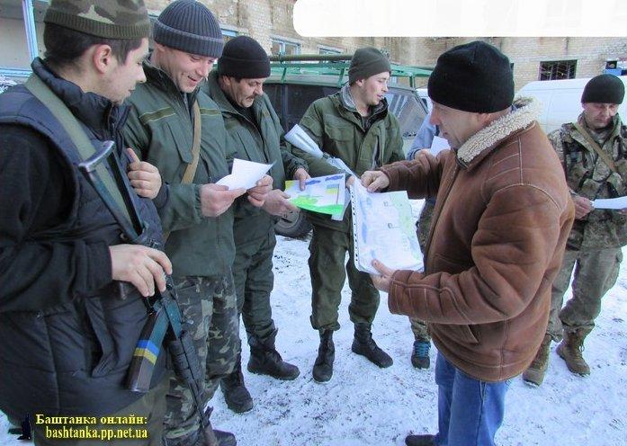 Володимир Гевкалюк роздає військовим-землякам малюнки від дітей Привільненської ЗОШ